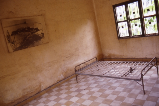When the Vietnamese army took Phnom Penh in 1979 they found the prison evacuated. A few dead prisoners were still there, chained to bedframes in some of the rooms. This bed has been left as it once stood, and a picture of the dead prisoner hangs on the wall beside it.