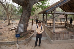 Our Cambodian guide Adam by the tree the Khmer Rouge used to kill small children. They would be picked up by their legs, and their heads would be crushed against the tree. Their bodies would be dumped in what is now the fenced area to the right.