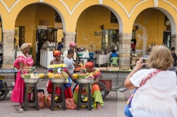 The fruit sellers, dressed in colorful costumes, expect to get paid for being photographed. They are not amused by the lady to the right, also from our cruise, trying to steal a picture.