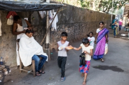 By mistake this picture was shot on the wrong shutter speed, but we still like the scene. A barber does his client in the narrow street while a mother and her young kids are passing.