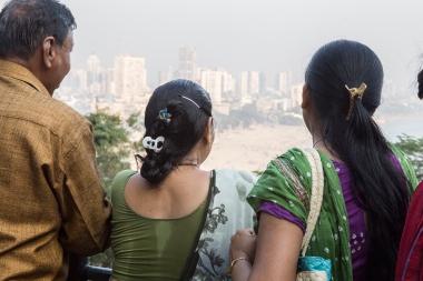 Three locals enjoying a scenic view of a Mumbai beach.