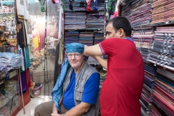 Our salesman shows DHH the sort of headgear the sultan and other nobilities of Oman wear.