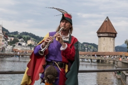 The Piper playing in front of the famous bridge of Luzern.