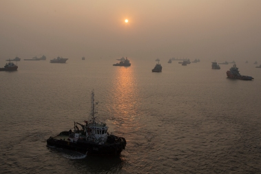 An early dusty sunrise over tugboats and the supply ships at the port of Mumbai.