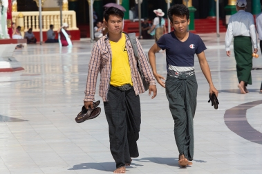 Two local men carrying their shoes, and wearing the male «skirt», a longyi. This is a sheet of cloth approximately 2 meters long 80 centimeters wide, worn around the waist.