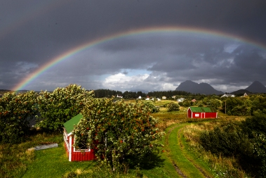 A rainbow framing the outhose and the barn of our family holiday home in Dønna.
